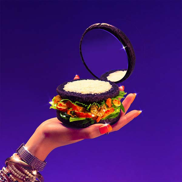 hand holding a brurger with a mirror