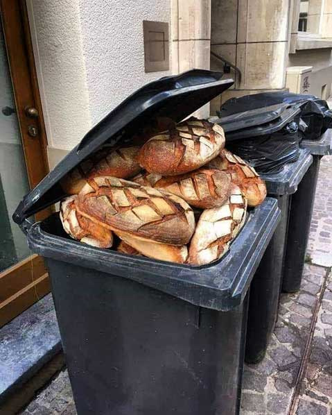 Black waste bin full of edible bread
